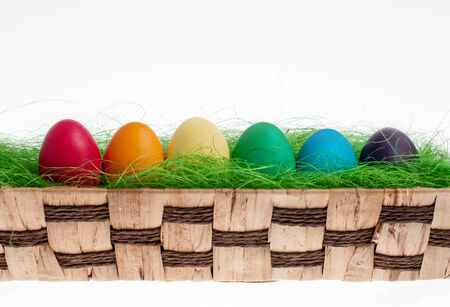 Six color Easter egg in a wicker basket photo