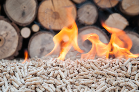 Pine pellets infront a wall of firewoods in flames Stock Photo