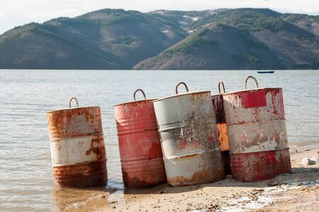 Five rusty fuel and chemical drums on the beach of a lake photo