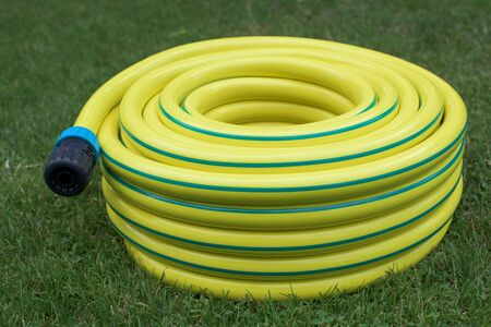 garden staff: Yellow hose-pipe with couplung on a grass