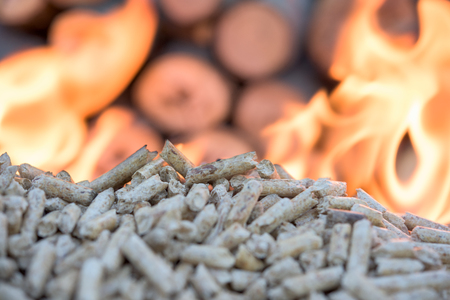 wooden Biomass in flames infront wall of wood Stock Photo