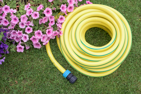 Yellow plastic  hose-pipe on the grass-