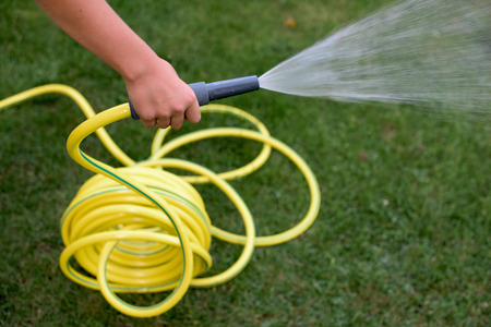 Yellow plastic hose pipe with sprayer at the end