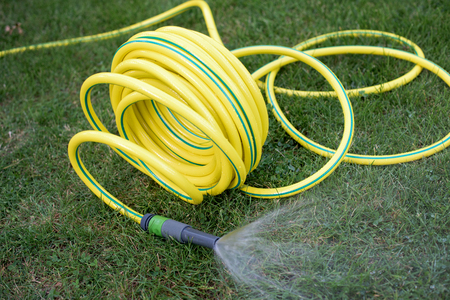 Yellow plastic hose pipe in the garden