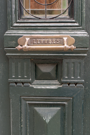Part of old green wooden door with mail box