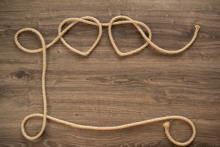 Two heart shapes made of rope on an old wooden panel