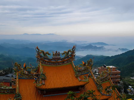 Traditional Chinese style roof in yellow with misty landscape hillside and seaview of the ocean