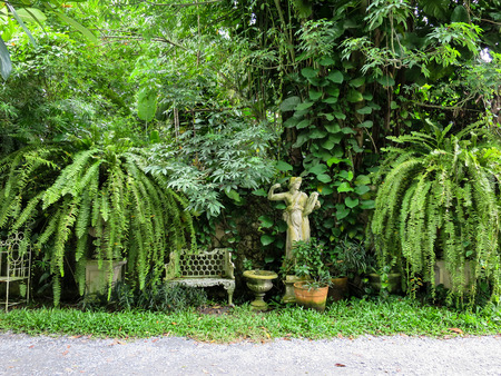 english style green garden with white bench, plant pots and lady musician sculpture Stock Photo