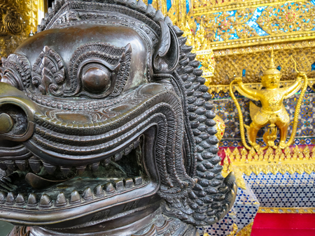Closeup black lion statue with golden garuda holding naga and ornamental decoration on temple wall background Stock Photo