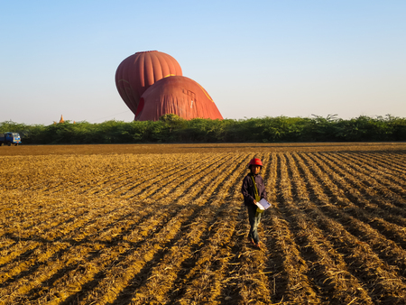 air dried: Bagan, Myanmar - January 26, 2015: An unidentified local boy standing on dried field with background of Balloons Over Bagan and clear sky.