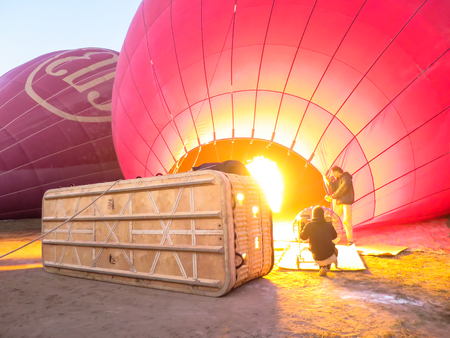 air dried: Bagan, Myanmar - January 26, 2015: Balloons Over Bagan using bright fire flame for hot air inflation process on ground. Editorial