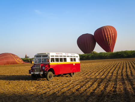 air dried: Bagan, Myanmar - January 26, 2015: Balloons Over Bagan vintage shuttle bus with dark red balloons, blue sky and pagoda background on dried field in the morning light after landing. Editorial