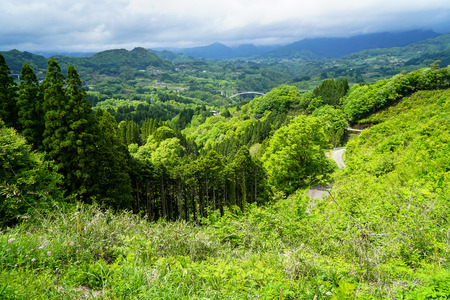 Lush greenery mountain panorama, bridge and town view from afar, Takachiho, Japan Stock Photo