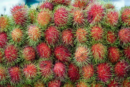 Pile of ripe sweet reddish rambutan fruit with pliable green hair in local market, Thailand