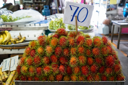 Pile of ripe sweet reddish rambutan fruit with pliable green hair in local market atmosphere, Thailand