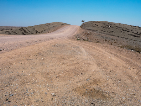 Road trip through rough dusty unpaved road with car tyre track through drought desert climate and rock mountain landscape with clear blue sky and dried tree, Namibia