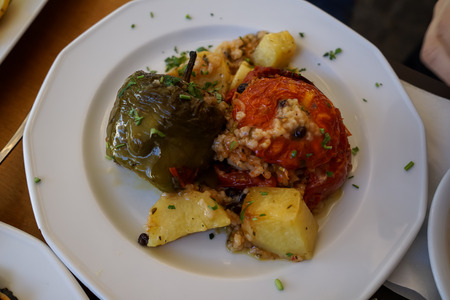 Traditional greek summer dish, baked stuffed vegetables, tomatoes, peppers and roasted potatoes with chopped mint, Athens, Greece