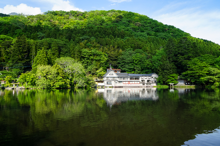 Beautiful abundant natural green mountain slope reflection on fresh lake Kinrinko with buildings during springtime, Yufuin, Japan