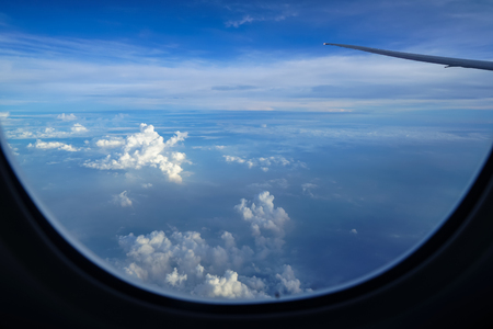 Flying on the plane seeing beautiful sunrise light on abstract white cloud and shades of blue sky background with airplane wing and blurred window frame foreground
