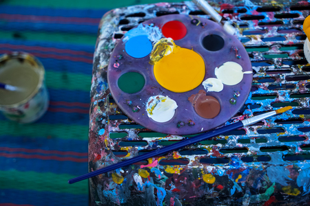 Circular painting palette full of colorful acrylic paint placing next to paintbrush on stained stool with moving brush, water bottle and mat background, Thailand