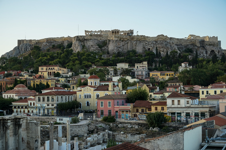 View of the Acropolis, Erechtheion, from Monasteraki Square through old town neighborhood buildings and Hadrians Library ruins, Athens, Greece Editorial