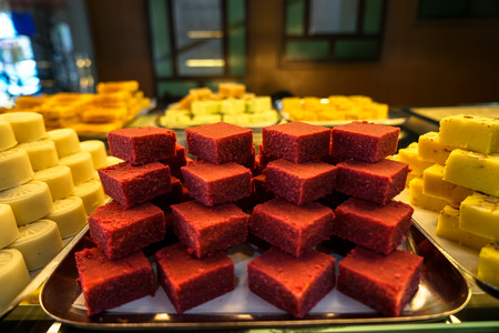 Trays full of stack colorful red Indian sweet dessert in bakery showcase, Little India, Penang, Malaysia