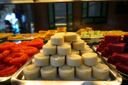 Trays full of stack sweet white, red, orange and yellow Indian dessert cake in bakery showcase, Little India, Penang, Malaysia Stock Photo