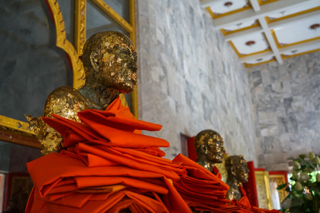 Sacred holy ancient sitting statue with golden leaf of vulnerable monks image, Luang Pho Chaem, with yellow robe offering in main hall at Wat Chalong, Phuket, Thailand Stock Photo