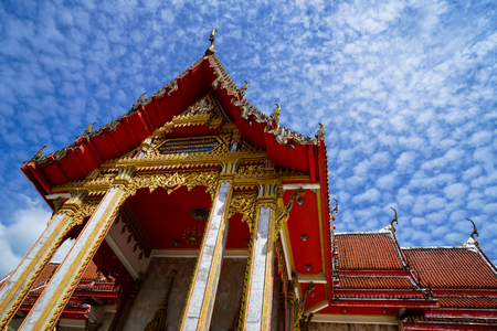 Beautiful sacred red roof main hall ornament of famous buddhist temple with blue sky and white cloud background, Wat Chalong temple, Phuket, Thailand