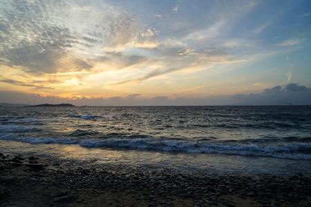 Beautiful sunset scene wavy seaview and natural rock beach with beautiful shades of soft orange and blue sky and abstract cloud background, Mykonos, Greece Stock Photo