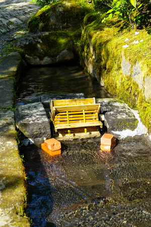 Beautiful fresh water canal ditch or natural gutter cover with green moss and lichen with traditional bamboo moving water turbine on sunshine day, Kurokawa onsen town, Japan