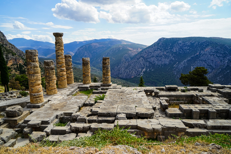 Beautiful view of temple of Apollo with green olive groves valley, Parnassus mountain and blue sky background, Delphi, Greece Stock Photo