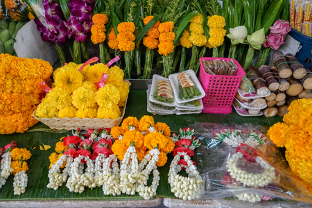 Varieties of Thai style temple offering including garlands made of white jasmine, crown flower, red rose and yellow marigold, flower and green leaves sets and betel nut tray in local market, Thailand