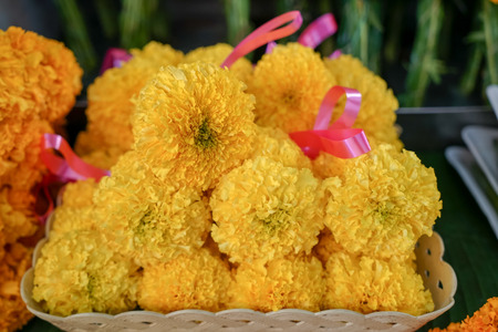 Fresh Thai style flower garlands made of bright yellow marigold with pink ribbon selling on basket in local market, Thailand