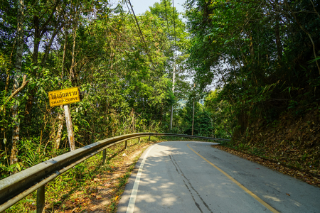 Yellow sharp curve warning road sign along local asphalt road through natural green forest mountain, Chiangmai, Thailand