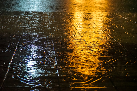 Abstract raindrop and spatter water on pavement floor with yellow and white light reflection at night, Bangkok
