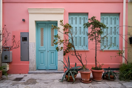 Scene of beautiful urban building facade background in pastel pink plaster paint wall, light blue entry door and windows with green plant pots, Athens, Greece Standard-Bild