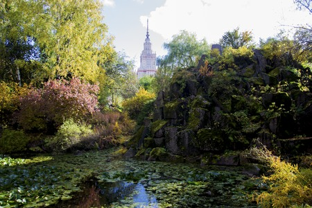 mysterious pond in the botanical garden of Moscow University. autumn landscape. water, rocks and blue sky