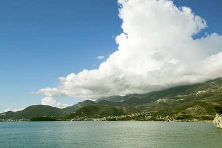photo of a sea landscape with mountains and clouds on the horizon