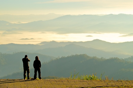 moutains: Silhouette of two tourists looking at the beautiful view of moutains in fog at dawn; Tourist attraction point in Maehongson, the north of  Thailand