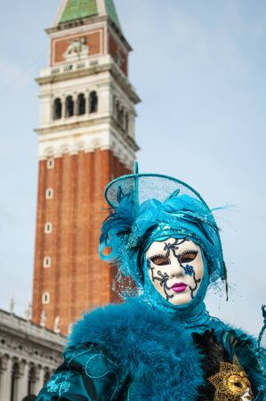 Blue venice mask costume san marco bell tower background Stock Photo