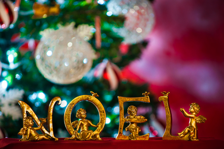 Cherub angels NOEL statuettes in gold with Christmas tree in background Imagens