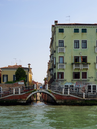 Old bridge with metal ramp over a canal, Venice, Veneto, Italy flanked by a colourful yellow house and palazzo, Unesco listed World Heritage Site