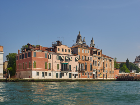 Palazzos or Venetian palaces on the Giudecca Canal, Venice, Italy with a restaurant deck viewed across the water