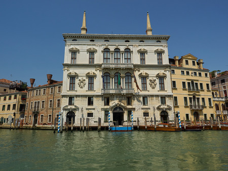 Exterior facade of an ancient palace or palazzo on the Grand Canal, Venice, Italy with private moorings in front