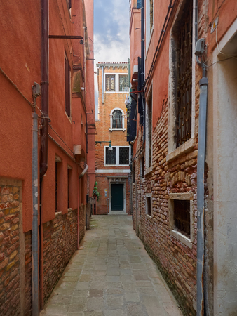 Narrow passage between colorful houses, Venice, Veneto, Italy, a popular tourist destination and UNESCO World Heritage Site Editorial