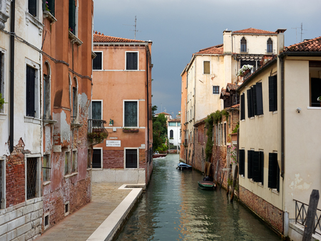Quiet back canal with historic residential buildings and reflections on the water, Venice, Veneto, Italy