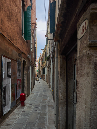 Narrow deserted walkway between houses, Venice, Italy with red fire hydrant and ancient buildings Editorial