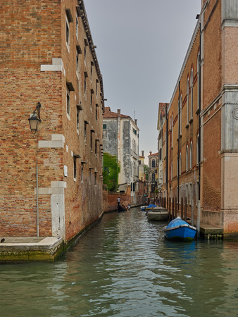 Quiet back canal with moored boats and ancient brick architecture, Venice, Italy with a gondola in the distance Editorial