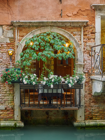 Old arched balcony with flowers in a wall with exposed brickwork on a canal, Venice, Italy, a popular tourist destination Editorial